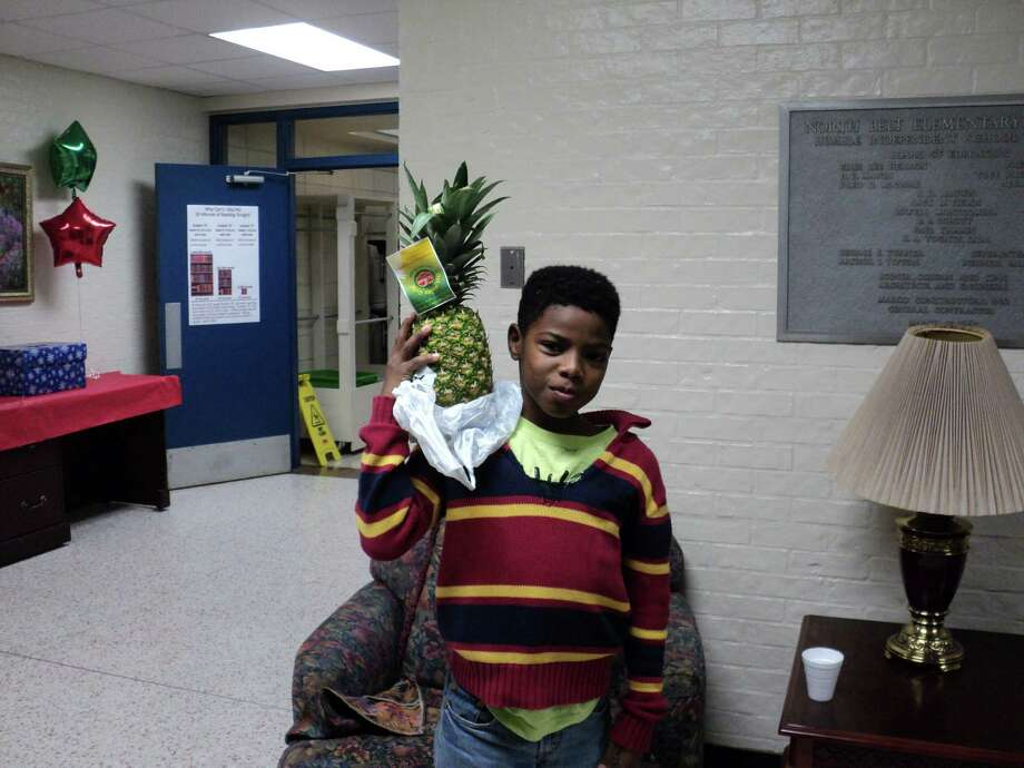North Belt Elementary fifth-grader Bray'veon Murray shows off one of the truck full of fresh fruits donated to the school by the Houston Food Bank. Photo: Photo By Humble Independent School District