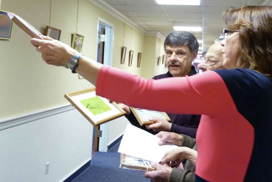 Sherri Steeneck, co-chairman of the Fairfield Arts Advisory Council, consults with Paul Murcko III, as they prepare an exhibit of his photographs at Sullivan Independence Hall. With them is Murcko's father, Paul Murcko II. Photo: Genevieve Reilly / Fairfield Citizen