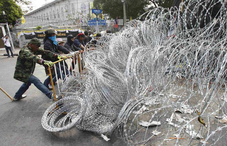 Anti-government protesters install a wire barricade during a rally near the Interior Ministry in Bangkok February 10, 2014.   REUTERS/Chaiwat Subprasom (THAILAND - Tags: POLITICS CIVIL UNREST) Photo: Chaiwat Subprasom, Reuters