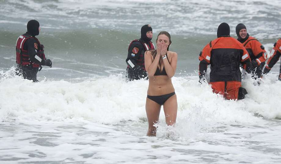 Saltwater daffy:Wendy Bell wades back out of the icy Atlantic surf during the Polar Plunge Winter Festival, a 