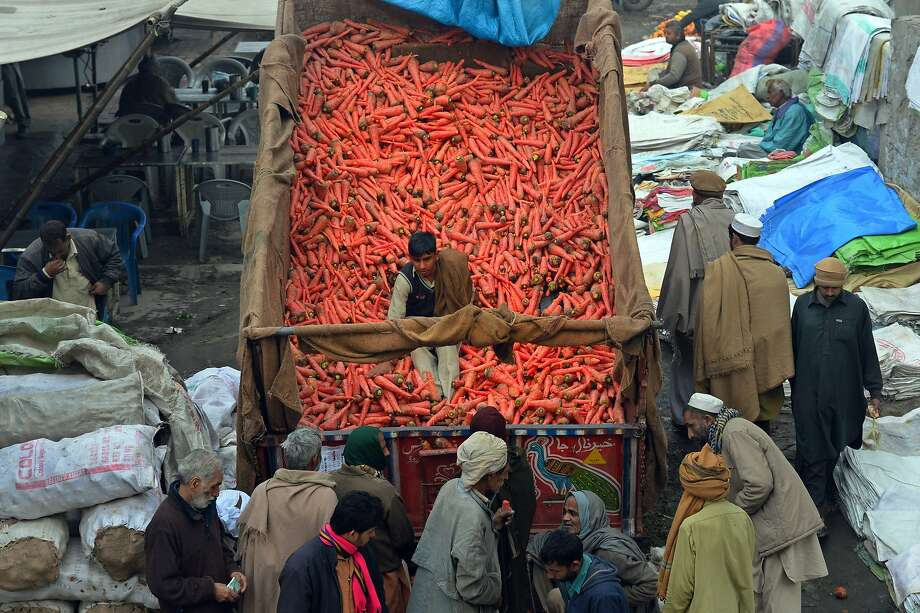 No extra charge for warming:A Pakistani vegetable vendor sits on some of the carrots he sells out of his truck in Lahore. Photo: Arif Ali, AFP/Getty Images