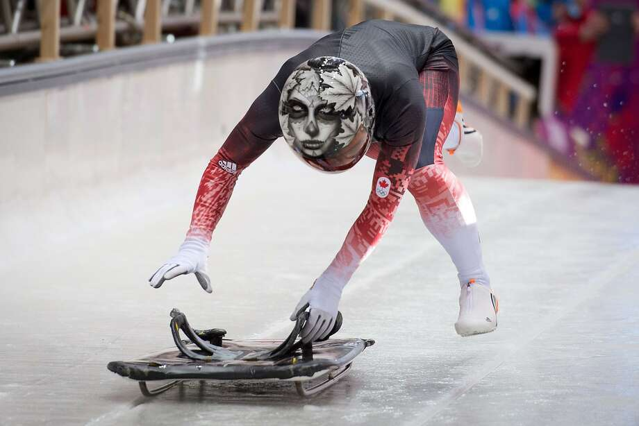 Spooky skeleton: Canada's Sarah Reid leaps onto her sled during an Olympics skeleton training session at 