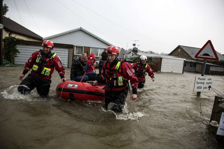 A rescue crew evacuates residents from flooded riverfront homes in Walton-on-Thames, England. Photo: Oli Scarff, Getty Images