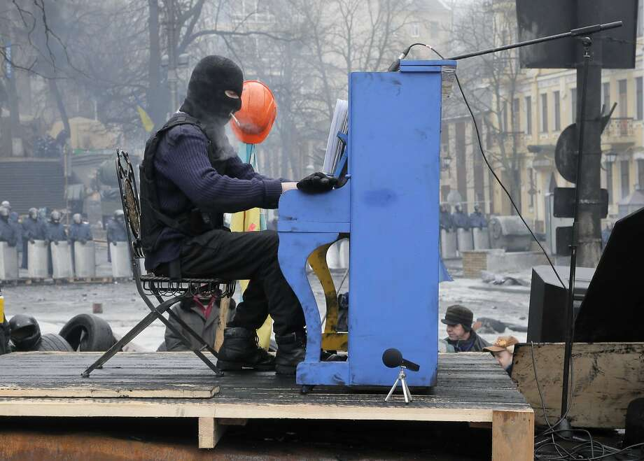 An opposition supporter plays the piano on a barricade in front of riot police in Kiev, Ukraine. Photo: Efrem Lukatsky, Associated Press