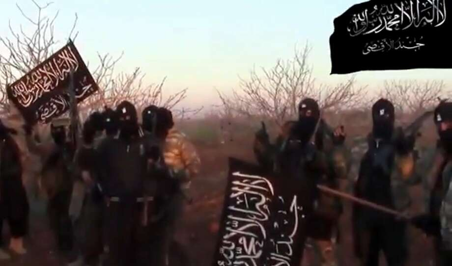 "An image grab taken from a video uploaded on YouTube on February 9, 2014 purportedly produced by Jund al-Aqsa, an Islamist Brigade part of the opposition coalition Islamic Front bloc, shows members of its forces holding its unit's flag on the outskirts of the village of Maan, an Alawite village in Syria's central Hama province. The Syrian Observatory for Human Rights, a Britain-based monitoring group said opposition fighters from Islamist brigades including Jund al-Asqa were behind the deaths of over 21 civilians and 20 pro-regime fighters. AFP PHOTO / YOUTUBE == RESTRICTED TO EDITORIAL USE - MANDATORY CREDIT ""AFP PHOTO / YOUTUBE "" - NO MARKETING NO ADVERTISING CAMPAIGNS - DISTRIBUTED AS A SERVICE TO CLIENTS FROM FROM ALTERNATIVE SOURCES, THEREFORE AFP IS NOT RESPONSIBLE FOR ANY DIGITAL ALTER  ===DSK/AFP/Getty Images Photo: Dsk, AFP/Getty Images"