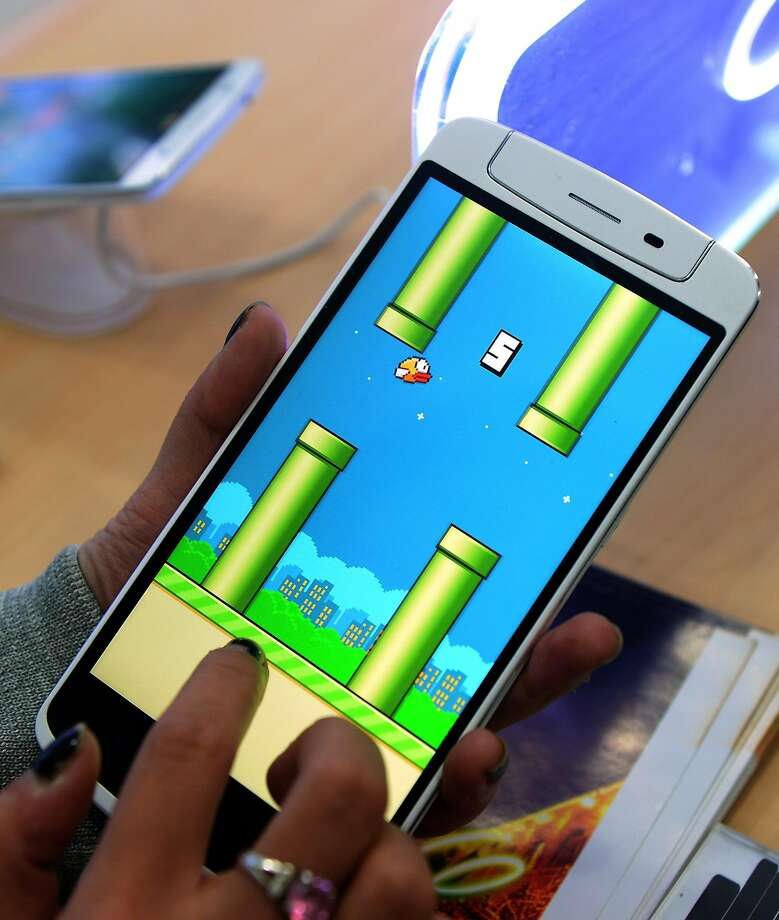 "An employee plays the game ""Flappy Bird"" at a smartphone store in Hanoi. Photo: Hoang Dinh Nam, AFP/Getty Images"