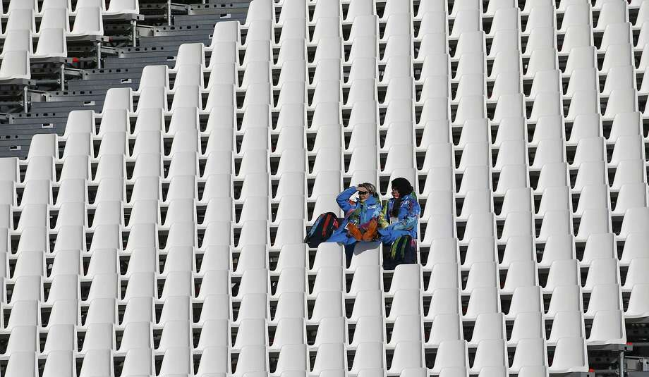 A large swath of empty seats surrounds two spectators during the third training session for the men's downhill-skiing event. Photo: Leonhard Foeger, Reuters