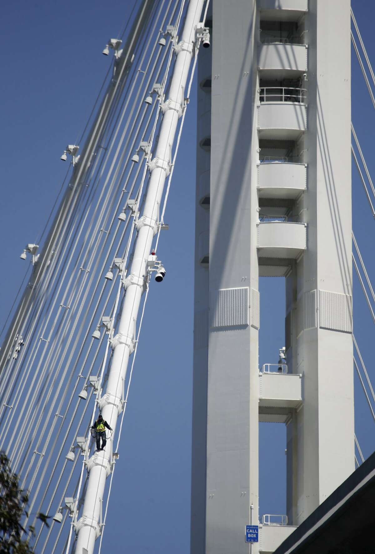 A construction worker climbs down on the main cable of the new Bay Bridge while sections of the temporary bike path are constructed in San Francisco, Calif. on Thursday, Aug. 22, 2013. Caltrans will shut down the Bay Bridge for five days over the Labor Day weekend to connect the new eastern span to the East Bay and Yerba Buena Island.