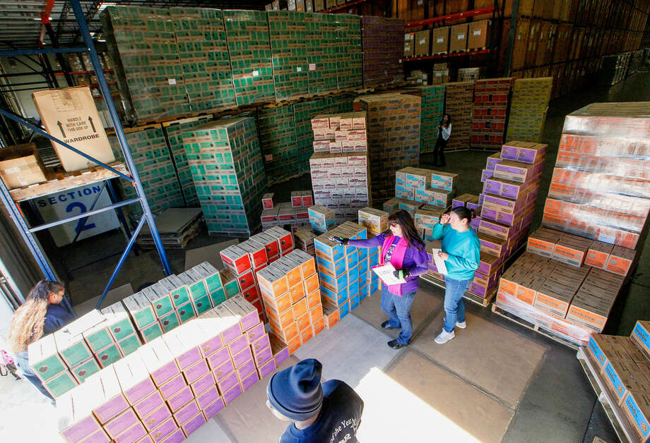 Kathryn Foley, center, confirms Girl Scout Troop 454's order with Cynthia Michaud, right, at the warehouse at 17257 Green Mountain Road late last month. Photo: Marvin Pfeiffer / Southside Reporter / Prime Time Newspapers 2014