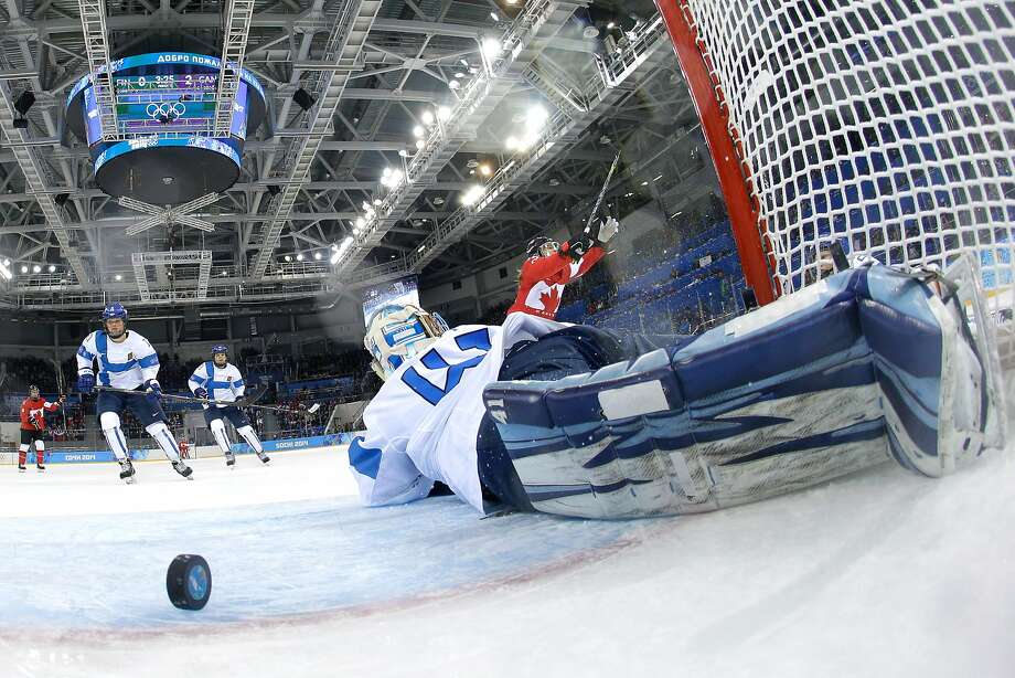 Canada's Rebecca Johnson (right, in red) gets the puck past Finland's goalie, Noora Raty. Finland lost 3-0 to Canada on Monday after falling 3-1 to the United States in its opening game. Photo: Pool, Getty Images