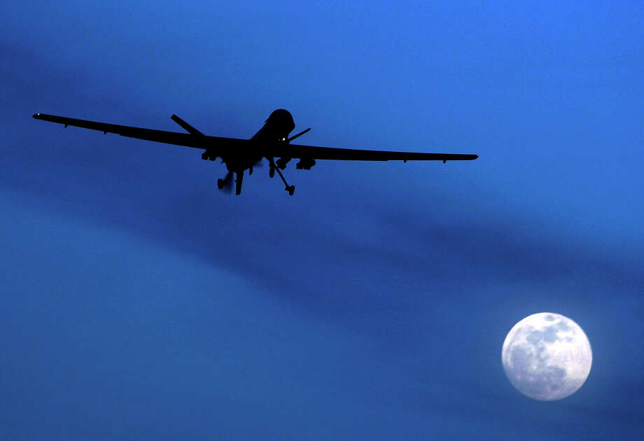 FILE - In this Jan. 31, 2010 file photo an unmanned U.S. Predator drone flies over Kandahar Air Field, southern Afghanistan, on a moon-lit night. An American citizen who is a member of al-Qaida is actively planning attacks against Americans overseas, U.S. officials say, and the Obama administration is wrestling with whether to kill him with a drone strike and how to do so legally under its new stricter targeting policy issued last year. The CIA drones watching him cannot strike because he's a U.S. citizen and the Justice Department must build a case against him, a task it hasn't completed. And President Barack Obama's new policy says American suspected terrorists overseas can only be killed by the military, not the CIA, creating a policy conundrum for the White House.  (AP Photo/Kirsty Wigglesworth, File) Photo: Kirsty Wigglesworth, STF / AP