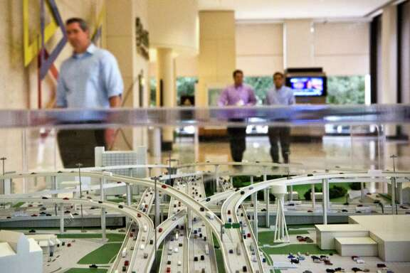 """Professionals at the Two Allen Center in downtown Houston walk by a large model of the Beltway 8 during an art exhibition titled """"The Art of Transportation"""" organized by the Houston-Galveston Area Council Transportation Department, Monday, Feb. 10, 2014."""