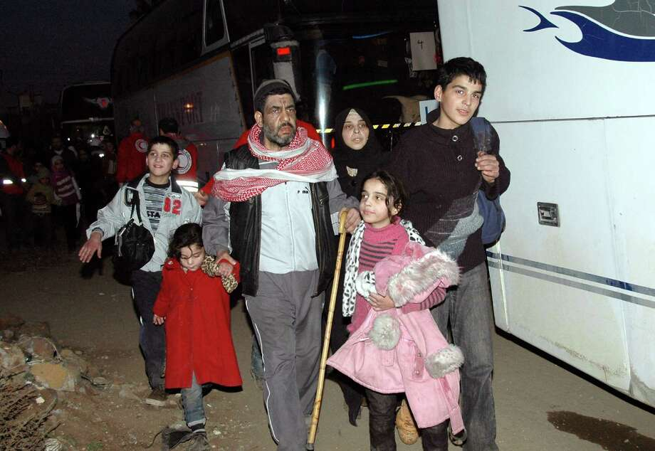Syrian citizens walk toward a bus to evacuate the battleground city of Homs, Syria. A Syrian Red Crescent official says around 300 more people were evacuated Monday from besieged rebel-held neighborhoods. Photo: HOPD / SANA