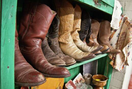 Cowboy boots line a shelf in Antiques on the Square, an antiques store in Uvalde. Photo: JOSHUA TRUDELL, FOR THE EXPRESS-NEWS / SAN ANTONIO EXPRESS-NEWS