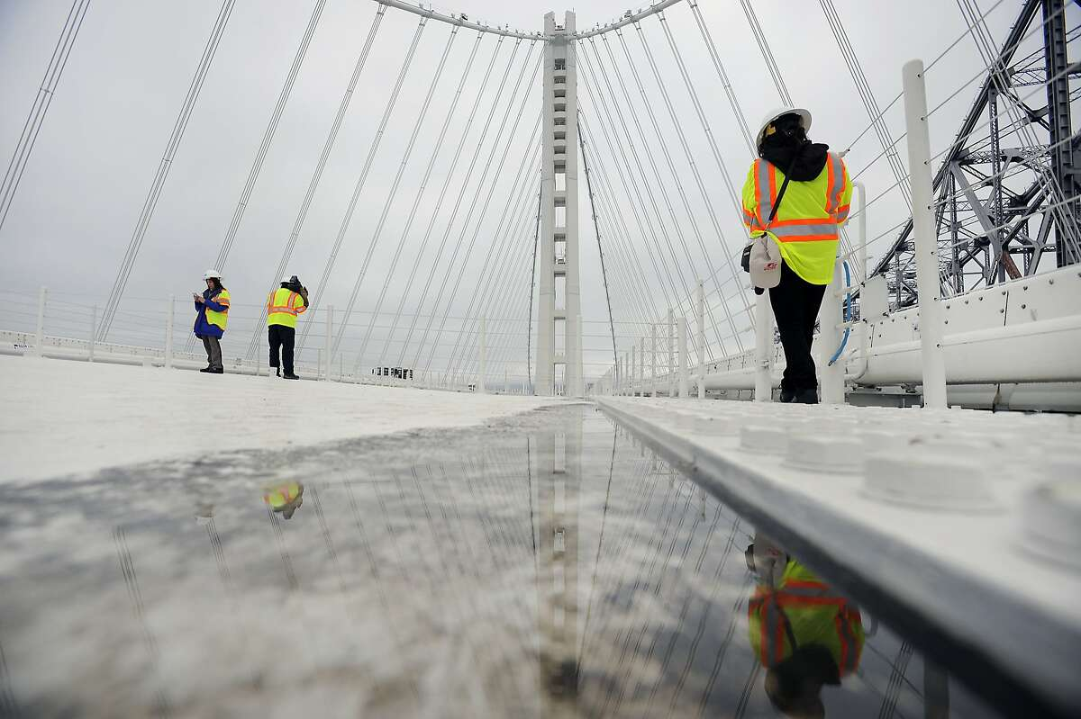 Members of the media are seen on top of the Eastern span of the Bay Bridge during a tour to see the newly discovered leaks in the roadway, in Oakland, CA Monday, February 10, 2014.