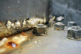 Rust and corrosion from a puddle of water are seen next to bolts in one of the hollow steel box girders that make up the roadway of the Eastern span of the Bay Bridge in Oakland, CA Monday, February 10, 2014.