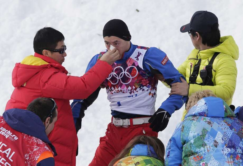 China's Liu Zhongqing, center, is assisted after crashing during freestyle skiing aerials training at the Rosa Khutor Extreme Park at the 2014 Winter Olympics, Monday, Feb. 10, 2014, in Krasnaya Polyana, Russia. (AP Photo/Andy Wong) Photo: Andy Wong, Associated Press