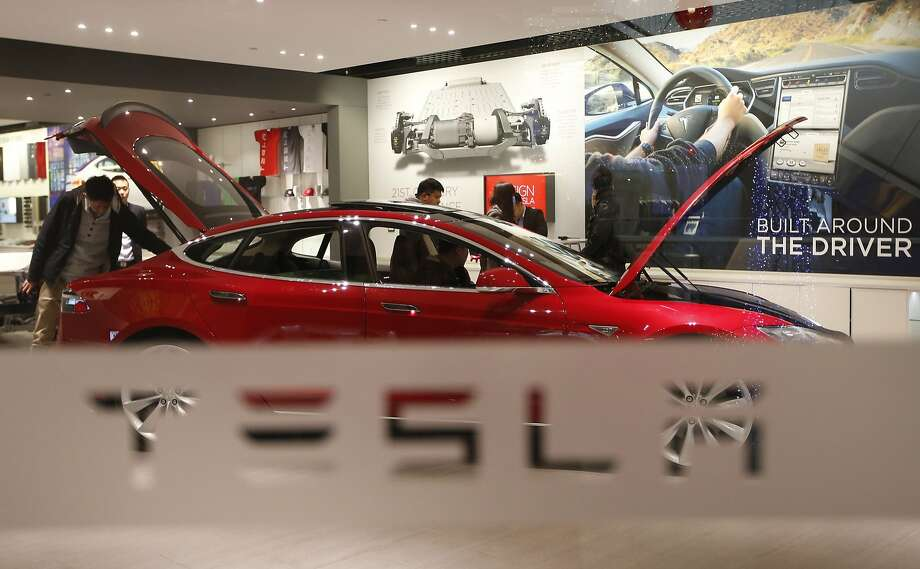 A man looks around Tesla Motors' Model S P85 at its showroom in Beijing January 29, 2014. A source tells The Chronicle that Apple's Adrian Perica met with Tesla CEO Elon Musk in Cupertino last spring, around the same time analysts suggested Apple acquire the electric cargiant. Photo: Kim Kyung-hoon, Reuters