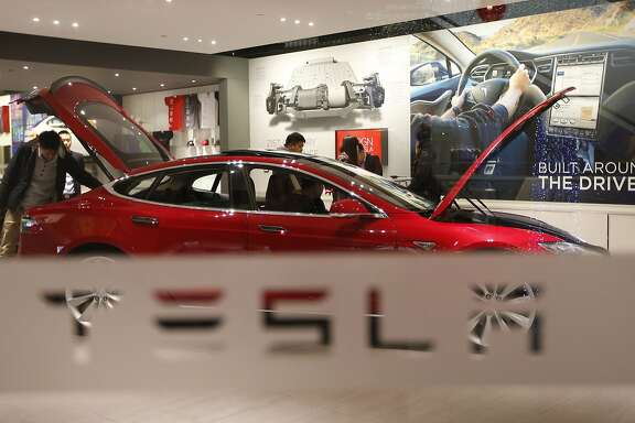 A man looks around Tesla Motors' Model S P85 at its showroom in Beijing January 29, 2014. A source tells The Chronicle that Apple's Adrian Perica met with Tesla CEO Elon Musk in Cupertino last spring, around the same time analysts suggested Apple acquire the electric car giant.
