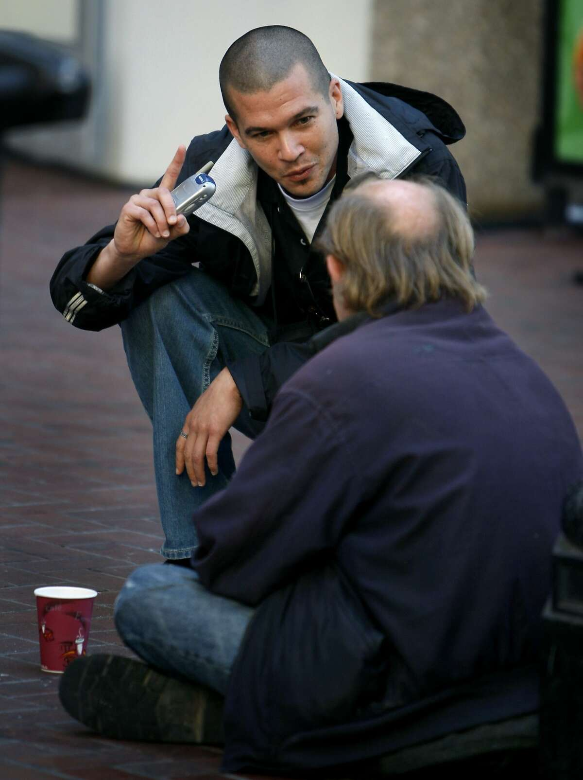 Nickolai Tamanaha, a case manager with the city's Homeless Outreach Team, makes contact with a potential client sitting on the sidewalk on Market Street corridor in San Francisco, Calif., on Friday, Sept. 19, 2008.