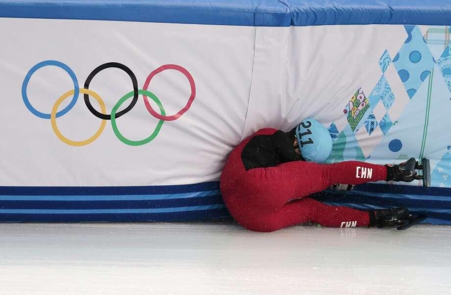 Shi Jingnan of China crashes in a men's 1500m short track speedskating heat at the Iceberg Skating Palace during the 2014 Winter Olympics, Monday, Feb. 10, 2014, in Sochi, Russia. (AP Photo/Ivan Sekretarev) Photo: Ivan Sekretarev, Associated Press