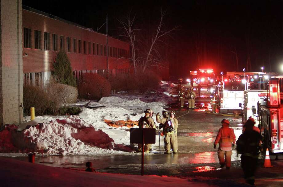 Emergency crews gather outside the New Hampshire Ball Bearings Inc. plant after an explosion early Monday rocked the facility in Peterborough, N.H. Photo: Jim Cole, STF / AP
