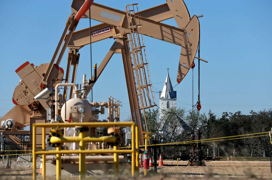 Oil pump jacks operate near the steeple of the Immaculate Conception Catholic Church in Panna Maria in December. Photo: San Antonio Express-News File Photo / ©2013 San Antonio Express-News