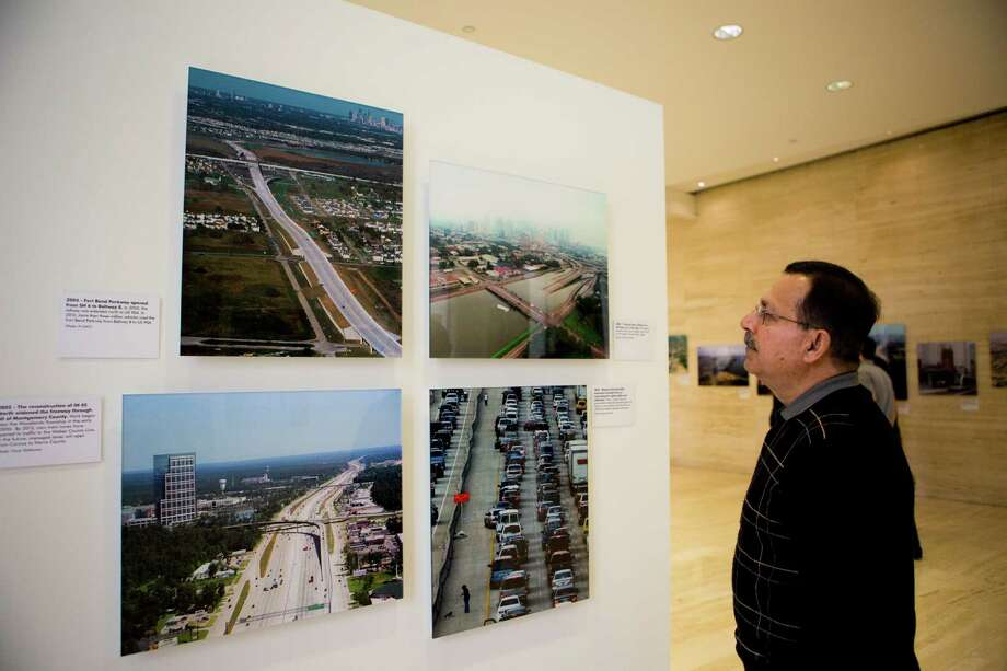 Rick Khadimally pauses to look at photographs showcasing the extensive damage to the Houston transportation system during Tropical Storm Allison in 2001. Photo: Marie D. De Jesus, Staff / © 2014 Houston Chronicle