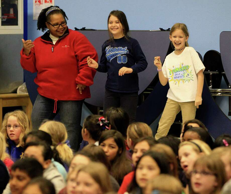 Instructional coordinator Cathy Cole dances with fourth-graders India Helzer, center, and Alice Heather during a Jazz & Poetry performance at Harvard Elementary School in the Heights. Photo: Karen Warren, Staff / © 2013 Houston Chronicle