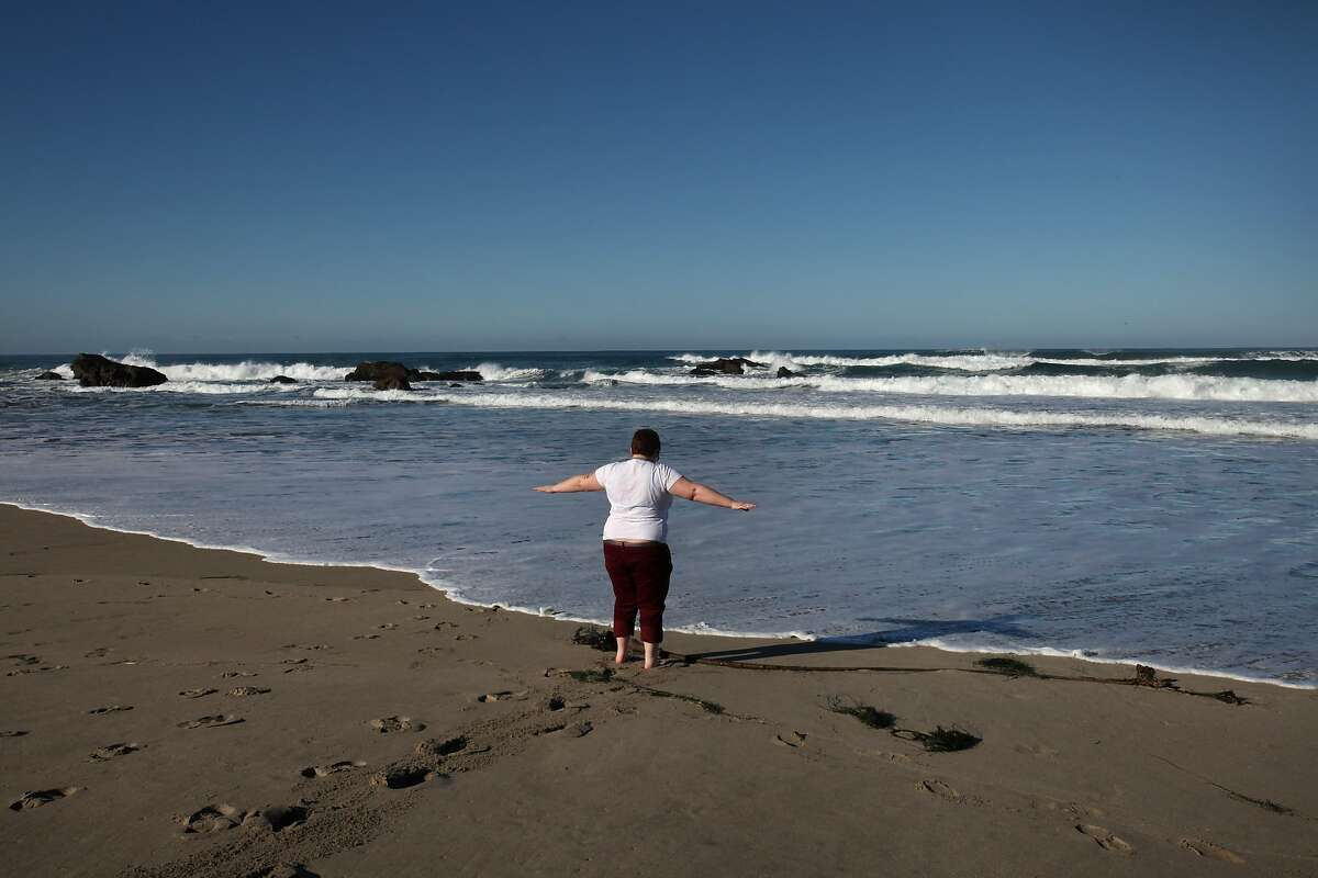 S.E. Smith, 29, allows the ocean to lap their feet at Pudding Creek Beach near Smith's home Feb. 1, 2014 in Fort Bragg. Smith says that after spending a week in the city, they like to visit the beach and dip their toes in the water. Smith identifies as Genderqueer; someone who sees gender as more of a spectrum. Because Smith doesn't identify with either normative genders, Smith is living between genders. Smith works as a freelance writer and editor and recently wrote a young adult fiction book about a transgendered teen that Smith is trying to get published. Smith says it was when they met like-minded individuals in college that they started questioning society's gender-norms. Currently, Smith has a places in both Fort Bragg and Berkeley so they can enjoy city life, as well as life near trees, the ocean and also be near Smith's father.