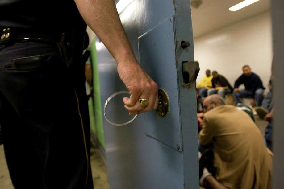 Men crowd into the outgoing holding cell at the Harris County Sheriff's Office Inmate Processing Division where about 400 inmates are received and released daily. Photo: Johnny Hanson, Staff / Houston Chronicle