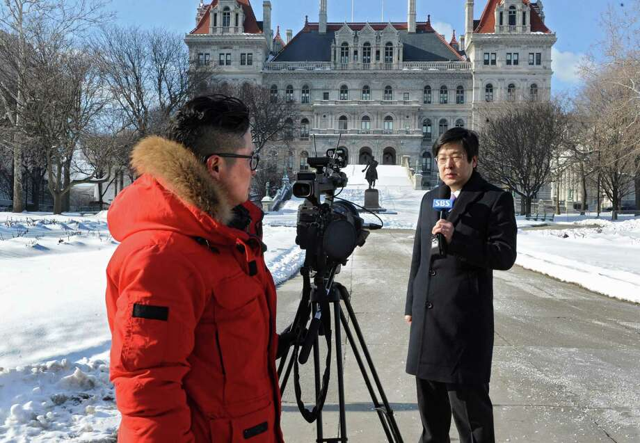 Cameraman Dowon Lee, left, and anchorman Jinho Park from Seoul Broadcasting System tape in front of the Capitol on Monday, Feb. 10, 2014, in Albany, N.Y. Earlier in the day there was a press conference where lawmakers gathered with Korean community groups from Queens in support of S6750, a bill that would require all new textbooks used in New York classrooms to also identify the body of water commonly known as the Sea of Japan as the East Sea. (Lori Van Buren / Times Union) Photo: Lori Van Buren / 00025691A