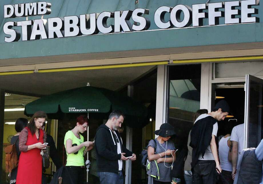 "People line up at ""Dumb Starbucks Coffee"" to score ""horrible"" coffee, but more importantly, a paper cup with a curious logo. Photo: Damian Dovarganes / Associated Press / AP"