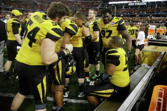 Missouri defensive end Michael Sam, right, is approached by teammates after causing the fumble that led to the game-clinching touchdown in the Cotton Bowl.