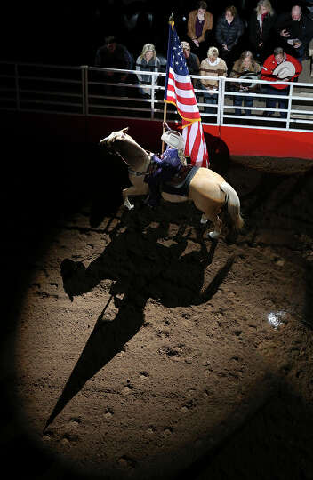 Kristen Bettis presents the American flag during the grand entry at the San Antonio Stock Show & Rod