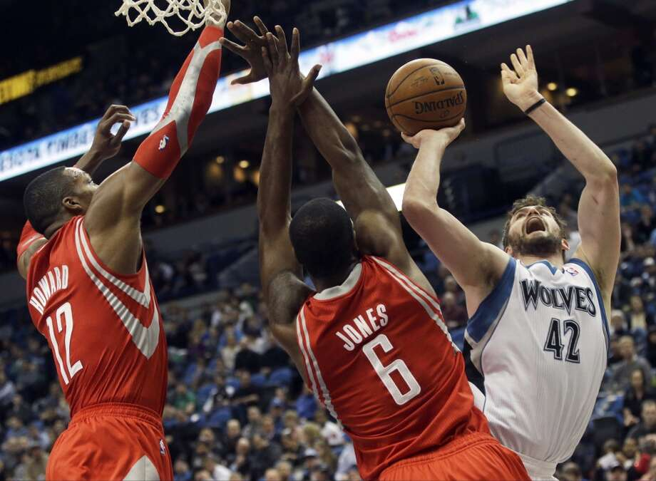 Kevin Love of the Timberwolves attempts a shot over Rockets forward Terrence Jones and center Dwight Howard. Photo: Jim Mone, Associated Press