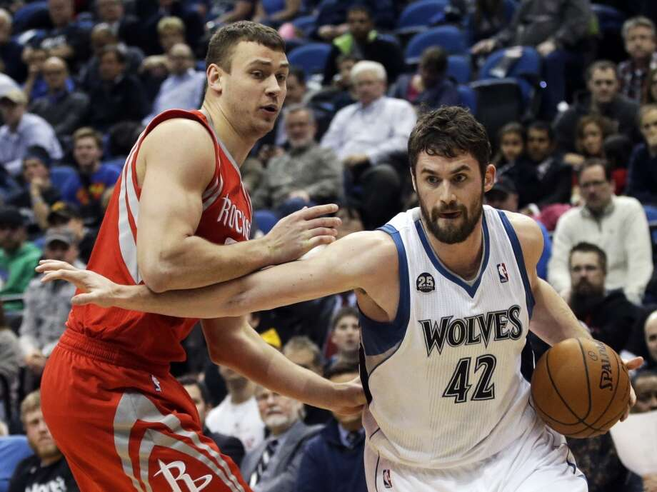 Timberwolves forward Kevin Love drives past Donatas Motiejunas of the Rockets. Photo: Jim Mone, Associated Press