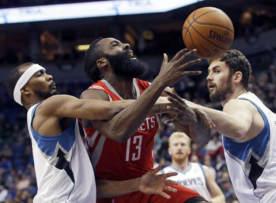 Rockets shooting guard James Harden is fouled by Corey Brewer of the Timberwolves as forward Kevin Love looks on. Photo: Jim Mone, Associated Press