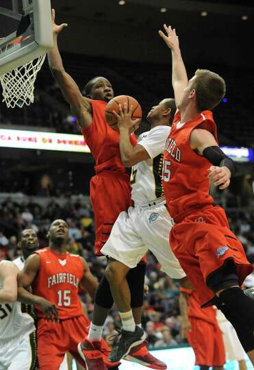 Siena's Evan Hymes is fouled as he drives to the basket during a basketball game against Fairfield a