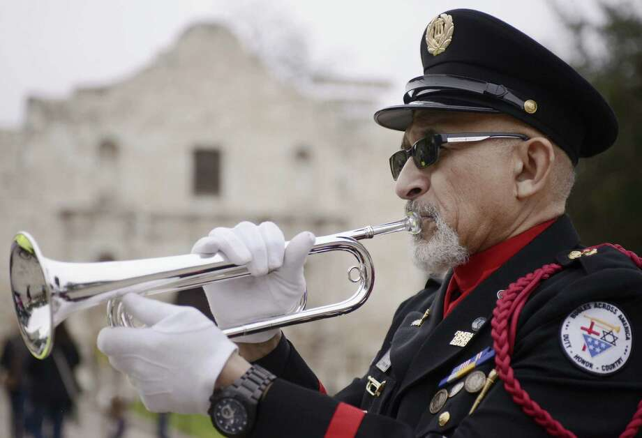 Auston O'Neill of Bugles Across America sounds taps in front of the Alamo during the Keep the Spirit of '45 Alive! touring RV's stop at Alamo Plaza. Photo: Darren Abate / For The San Antonio Express-News