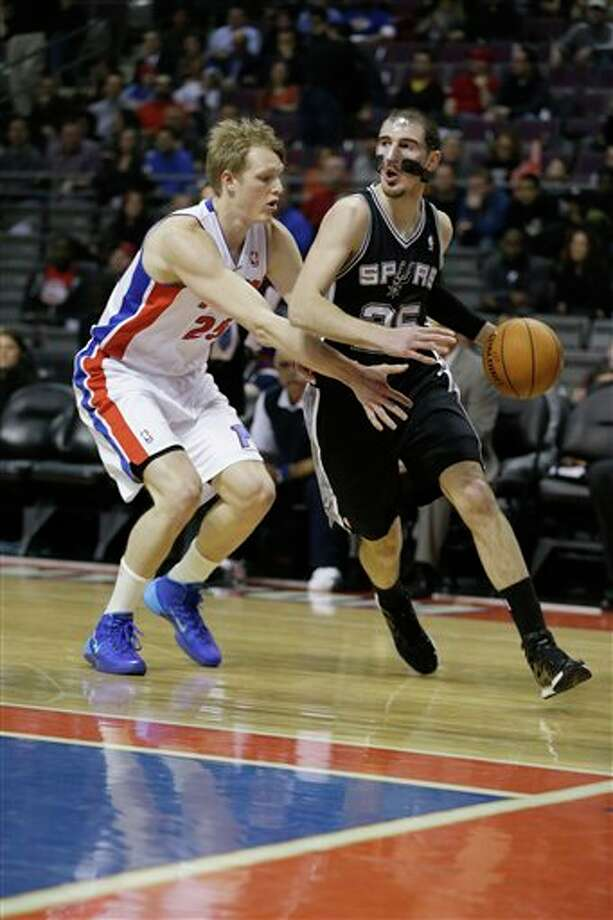 San Antonio Spurs guard Nando de Colo (25) of France is defended by Detroit Pistons forward Kyle Singler during the first half of an NBA basketball game at the Palace of Auburn Hills, Mich., Monday, Feb. 10, 2014. (AP Photo/Carlos Osorio) Photo: Carlos Osorio, AP / AP