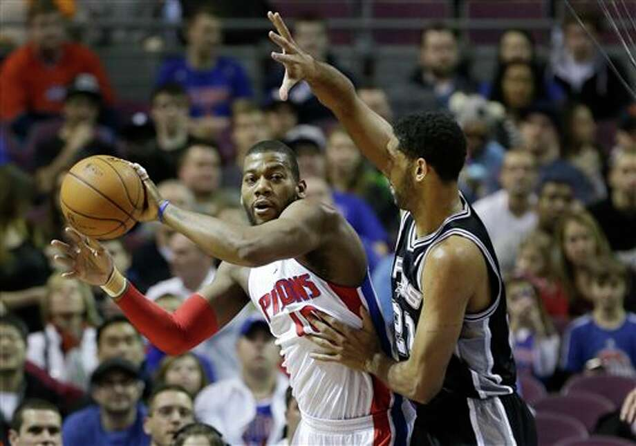 Detroit Pistons forward Greg Monroe (10) passes the ball as he is defended by San Antonio Spurs forward Tim Duncan (21) during the first half of an NBA basketball game in Auburn Hills, Mich., Monday, Feb. 10, 2014. (AP Photo/Carlos Osorio) Photo: Carlos Osorio, AP / AP