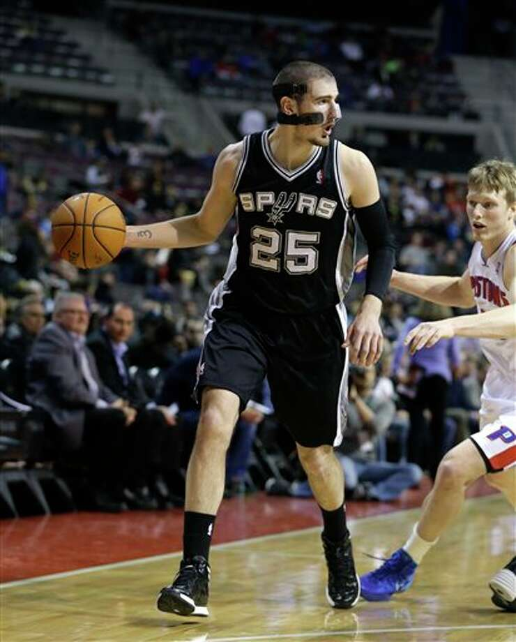 San Antonio Spurs guard Nando de Colo (25) of France looks to pass during the first half of an NBA basketball game against the Detroit Pistons at the Palace of Auburn Hills, Mich., Monday, Feb. 10, 2014. (AP Photo/Carlos Osorio) Photo: Carlos Osorio, AP / AP