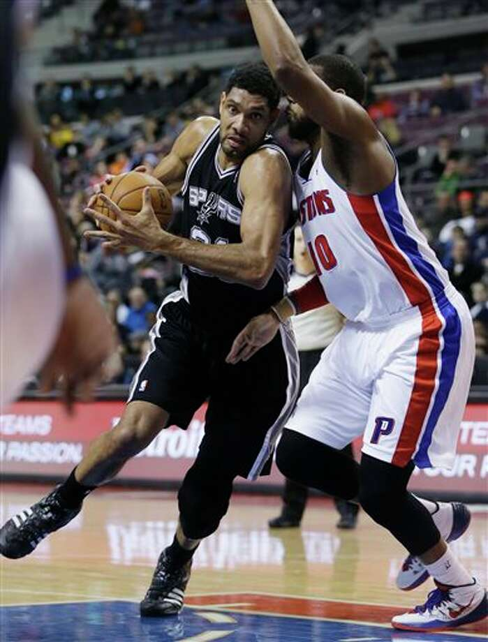 San Antonio Spurs forward Tim Duncan (21) drives on Detroit Pistons forward Greg Monroe (10) during the first half of an NBA basketball game in Auburn Hills, Mich., Monday, Feb. 10, 2014. (AP Photo/Carlos Osorio) Photo: Carlos Osorio, AP / AP