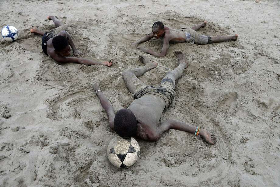 Three Garifuna children rest afer playing ball at the beach in El Triunfo de la Cruz, over the Caribbean Sea, 300 km north of Tegucigalpa, on February 10, 2014.      TOPSHOTS/AFP   PHOTO/Orlando SIERRA.ORLANDO SIERRA/AFP/Getty Images Photo: Orlando Sierra, AFP/Getty Images