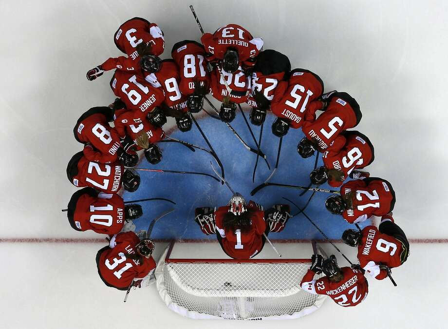 Canada's women's ice hockey team surrounds goalie Shannon Szabados before their women's ice hockey game against Finland