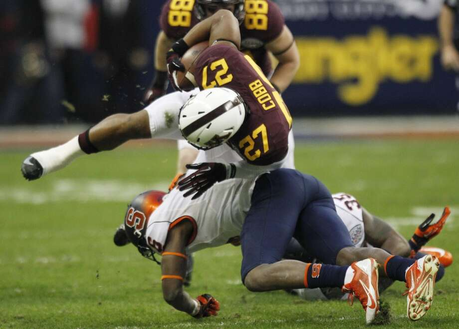 Minnesota running back David Cobb (27) is knocked off his feet by Syracuse safety Ritchy Desir (6) during the first quarter of the Texas Bowl at Reliant Stadium, Friday, Dec. 27, 2013, in Houston. ( Brett Coomer / Houston Chronicle ) Photo: Brett Coomer, Houston Chronicle