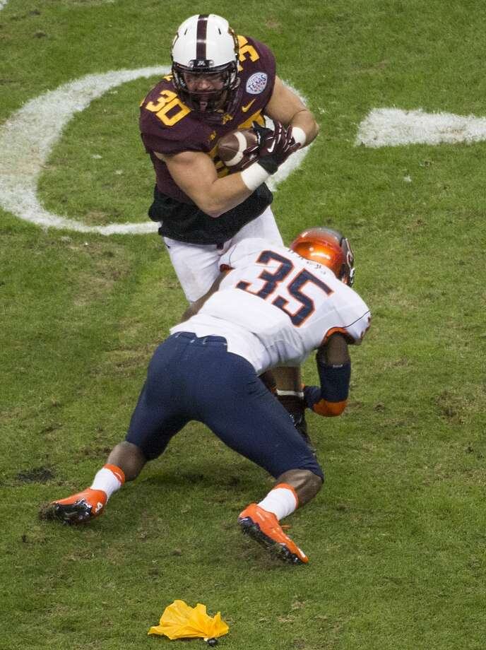 Minnesota fullback Mike Henry (30) is brought down by Syracuse linebacker Dyshawn Davis (35) during the first quarter of the Texas Bowl at Reliant Stadium, Friday, Dec. 27, 2013, in Houston. ( Smiley N. Pool / Houston Chronicle ) Photo: Smiley N. Pool, Houston Chronicle