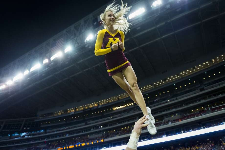 A Minnesota cheerleader is tossed into the air during the second half of the Texas Bowl at Reliant Stadium, Friday, Dec. 27, 2013, in Houston. ( Smiley N. Pool / Houston Chronicle ) Photo: Smiley N. Pool, Houston Chronicle