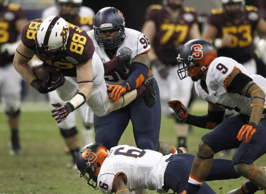 Minnesota tight end Maxx Williams (88) is tripped up by Syracuse safety Ritchy Desir (6) during the fourth quarter of the Texas Bowl at Reliant Stadium, Friday, Dec. 27, 2013, in Houston. ( Brett Coomer / Houston Chronicle ) Photo: Brett Coomer, Houston Chronicle